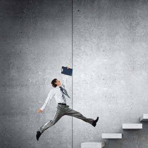 A businessman holding a clipboard is jumping up a flight of stairs