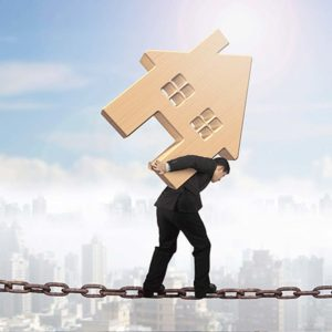 A real estate industry accountant is walking on a tight rope walking on a chain carrying a house block on his back