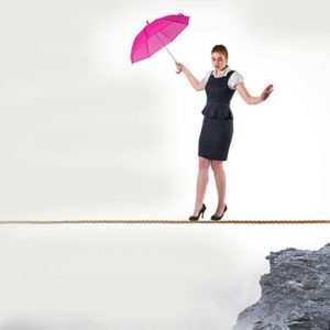 A woman accountant holding a pink umbrella is tight rope walking